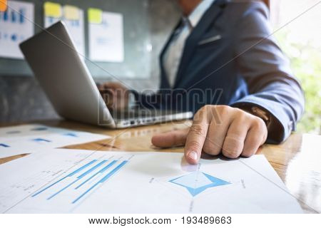Business executive pointing graph presentation to colleagues in office during meeting explaining consultation.