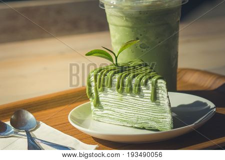 Close up green tea cake and matcha iced green tea on wooden salver with sunlight background in the morning. (Selective Focus)