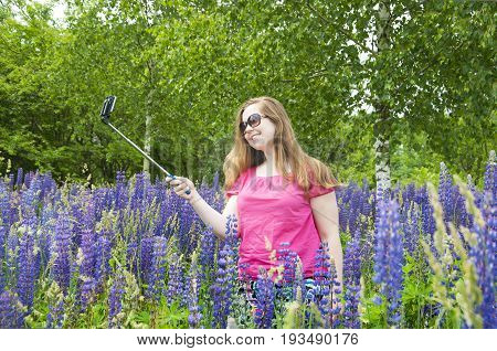 Young European red-haired girl in a pink blouse photographed themselves on selfie stick in a field of blooming lupines.