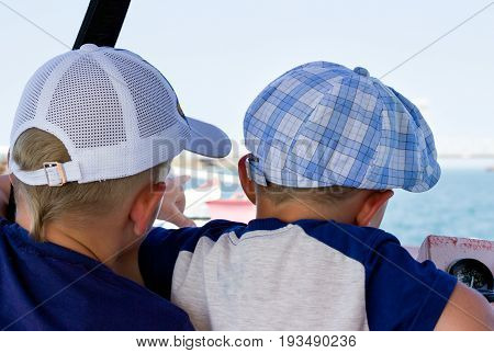 Two little boys are swimming on a boat by the sea they are watching the sea and one noticing something points to something interesting