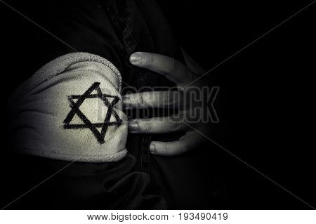hand with the badge of the star of David. The concept of the Holocaust stylized 1940s. The memory of the victims of the Holocaust. black and white retro photo
