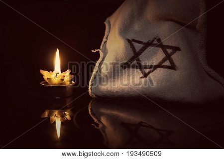 A burning candle next to the star of David on a black background. A symbol of remembrance of the victims of the genocide of the Jew in the third Reich in Germany.