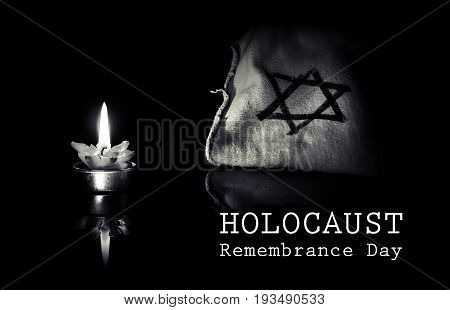 burning candle and the Star of David against a black background, We will never forget, the Jewish Holocaust and Heroism. Holocaust Remembrance day 27 January