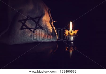 burning candle and the Star of David against a black background, We will never forget, the Jewish Holocaust and Heroism Remembrance Day
