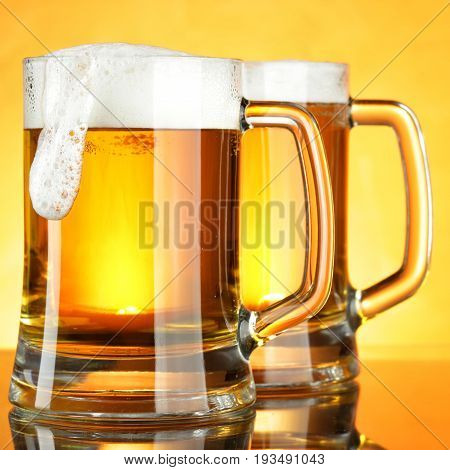 Beer mugs with froth close up with golden background