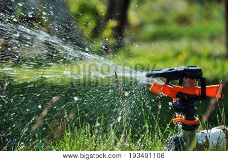 The process of watering a lawn with a sprinkler.