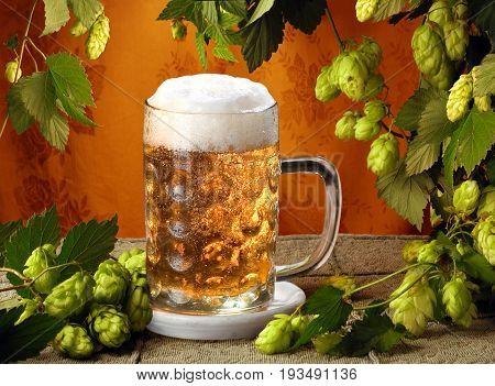 Beer, beer foam and hops on wooden background