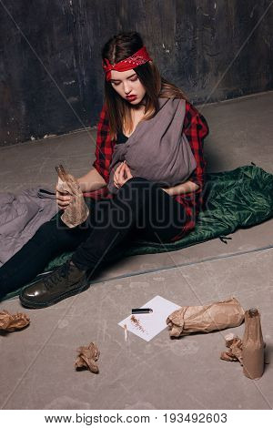 Poor alcoholic mother get drunk. Woman with baby holding bottle in hand. Maternal harm, youth lifestyle, social problem, negative addiction concept