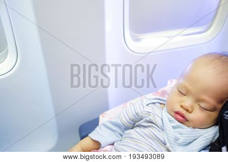 Adorable Baby Boy Sleeping On Airplane with copyspaceToddler boy sleeping on mother's laps while traveling in airplaneFlying with children. Mom and sleeping 10 months old baby:Shallow depth of field