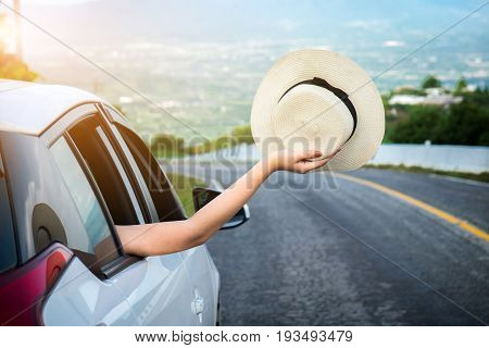 Relaxed happy traveler Young beatiful asian gilr holding hat weave and Reach out of the car at sunset and beautiful view with mountain road background.