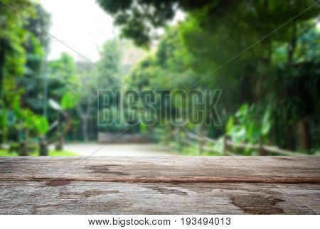 Selected focus empty old wooden table and green garden or forest blur background with bokeh image. for your photomontage or product display.