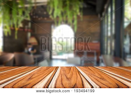 Selected focus empty brown wooden table and coffee shop cafe or restaurant blur background image. for your photomontage or product display.