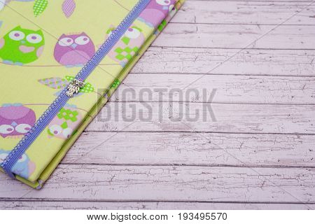 Beautiful handmade travel paper  folder with owl design lying on purple wooden background. Scrapbooking. Copy space.