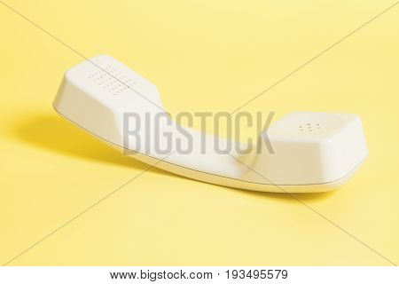 Telephone receiver on a yellow background .