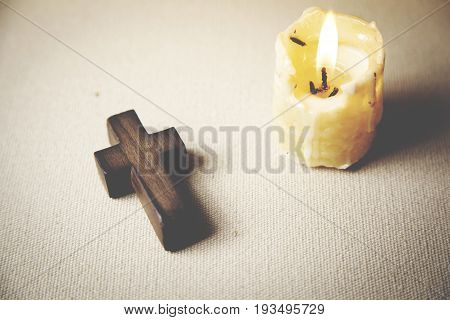 wooden cross and candle on white background