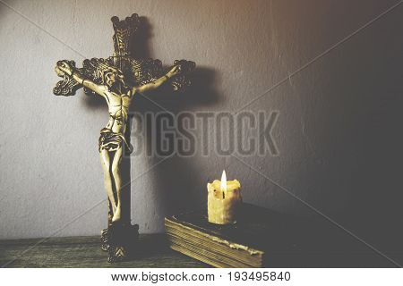 cross book and candle on wooden background