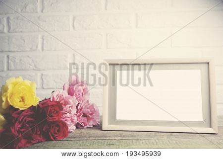 colorful roses and photo from on wooden table on brick wall background