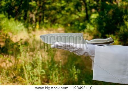 A waiter's hand in a white glove and with a white napkin holds a large metal knife made of silver metal with a metal handle on a blurred background of nature green bushes and trees