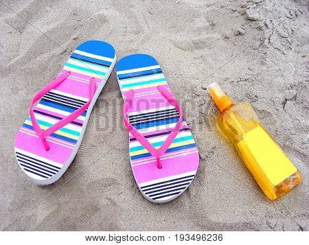 Summer time with flip-flops and sun-care milk on a sandy beach
