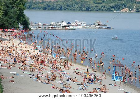 Novi Sad Serbia - July 31 2008: People enjoy swimming walking and sunbathing in the friendly environment on a beach called Strand on a Danube river. / Summer on the river Danube in Serbia