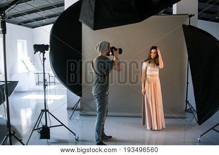 Photographer work in professional studio . Man taking shot of female model. Photo school, lookbook, fashion backstage concept