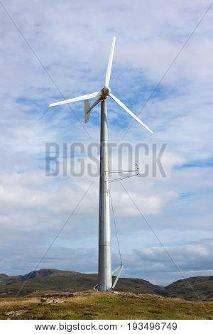 Single Wind Turbine in rural area against blue cloudy sky