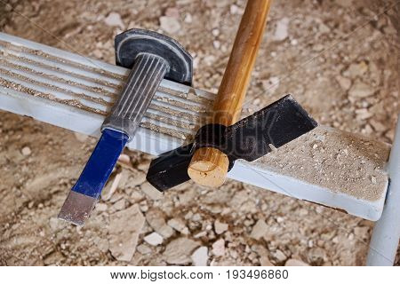 Hammer and chisel on ladder and rubble