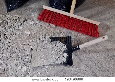 Broom and dustpan on a pile of construction rubble