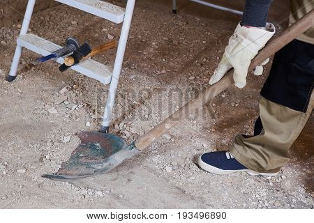 Worker cleaning construstion rubble with old spade
