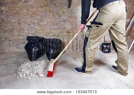 Worker sweeping rubble and dust with broom poster