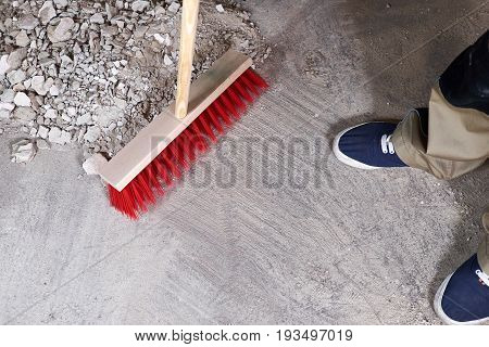 Workman sweeping the rubble on the floor with a broom
