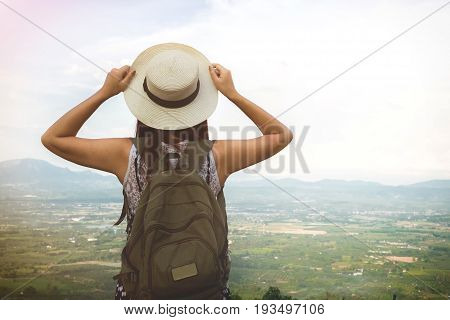 Relaxed happy traveler Young Hipster woman traveler with backpack holding hat weave and looking at beautiful view nature mountain background.