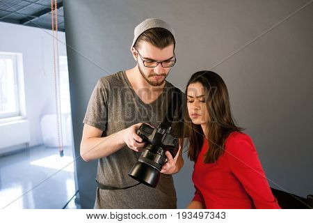 Model didn't like photos on camera. Photographer communicate with model on photoshoot. Man with camera show pictures to woman in red dress during the studio session.
