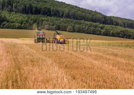 VALCHOV, CZECH REPUBLIC - JUNE 29: Combines harvesting grains and filling tractor trailer in summer on field June 29, 2017 in Valchov, Czech Republic