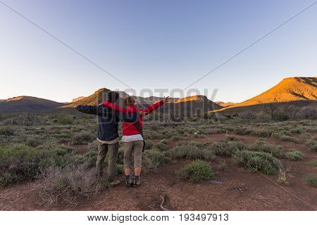 Hugging couple with outstretched arms watching the stunning view of the Karoo National Park at sunset travel destination in South Africa. Traveling people and adventure.