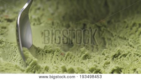 macro of pistachio ice cream being scooped with spoon, wide photo
