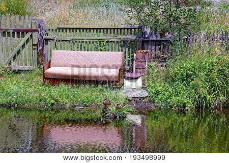 Old gray sofa in the grass on the lake shore