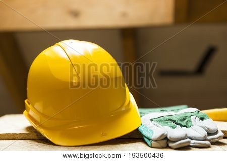 Yellow safety helmet and gloves on working surface at attic renovation site