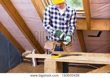 Handyman in yellow safety helmet with a tool belt. House renovation service. Attic renovation