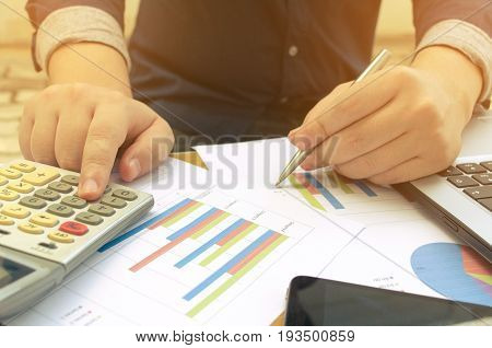 young accountant or business man working and writing with data sheet calculator laptop and smartphone finances and calculate on desk savings finances and economy concept sunlight effect