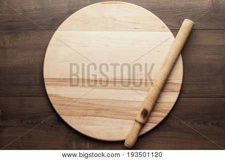 old wooden rolling pin and round board on brown table