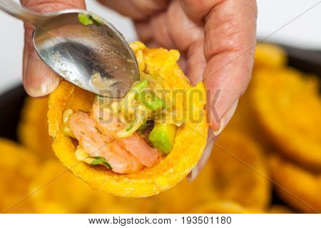 Close up of a woman filling a plantain cup with shrimp ceviche