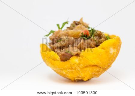 Plantain cup filled with refried beans on white background