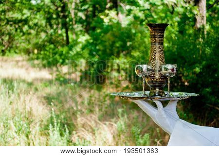 A waiter's hand in a white glove and a white napkin holds a metal table set with two wine glasses and a decanter of metal on a blurred background of nature green bushes and trees