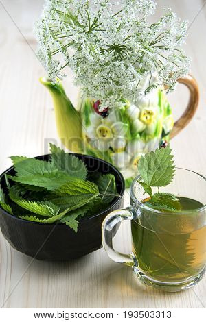 Nettle tea on the wood background leaves in the cup on a wooden table and wild flowers
