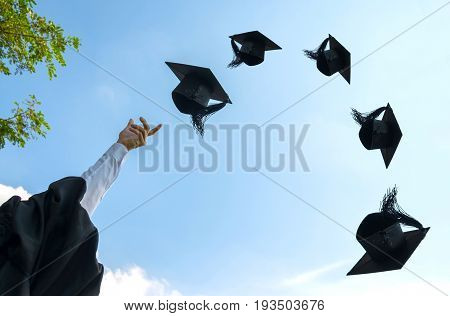 Graduation day Images of hand holding Caps or hat throwing in the air with sunshine day on blue sky background Happiness feeling Commencement day Congratulation Ceremony.