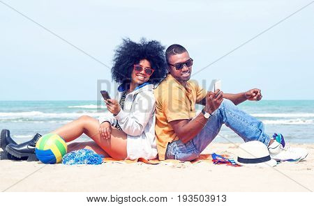 Young afro american couple having fun back to back on the beach using mobile phone - Attractive african models holding smartphone joyful summer moments sitting by ocean - Vintage filter modified ball