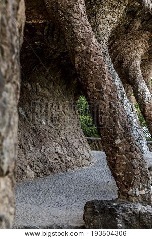 Passage with pillars at park Güell in Barcelona with vegetation vertical