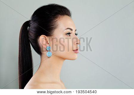 Closeup Fashion Portrait of Beautiful Model Woman wearing Blue Earrings. Pretty Young Face