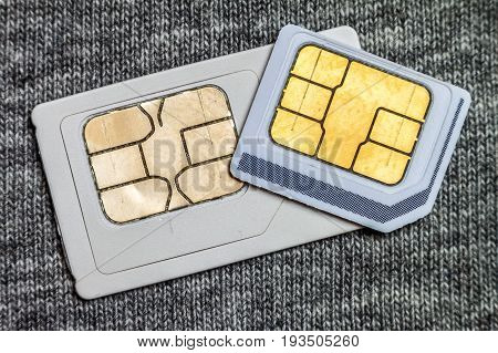 Set of mini and micro simcard. Isolated on grey cloth texture background